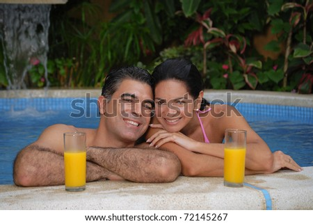 Young latin couple drinking orange juice in a swimming pool. - stock photo