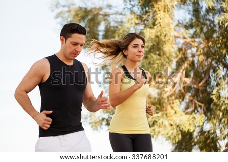 Young Latin couple in sporty outfit doing some exercise together at a park - stock photo
