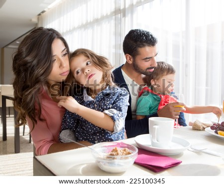 Young latin family having breakfast with kids