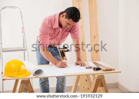 Young Latin man drawing and modifying a house design - stock photo