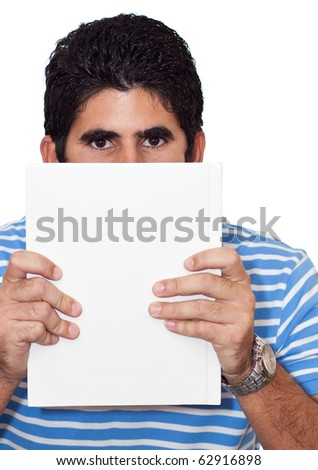 Young latin man hiding behind a book useful as copyspace isolated on a white background - stock photo