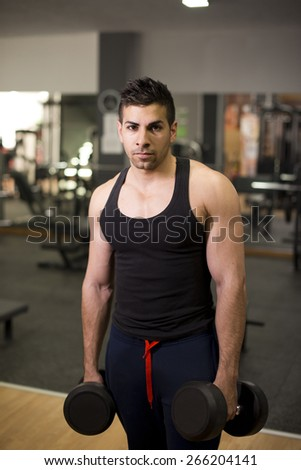 Young latin man posing at gym with dumbbells training biceps - stock photo