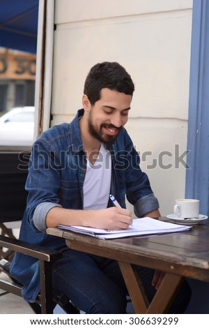 Young latin man studying at an outdoor cafe. Urban style. - stock photo