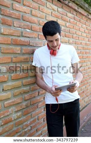 Young latin man using a tablet on the street.