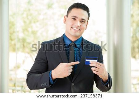 Young Latin man wearing a suit and holding and pointing at a credit card - stock photo