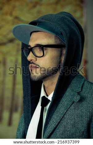 Young latin man wearing glasses and a hoodie side view closeup - stock photo