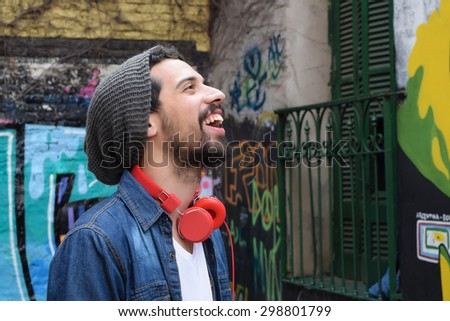Young latin man with red headphones. Trendy and urban style,