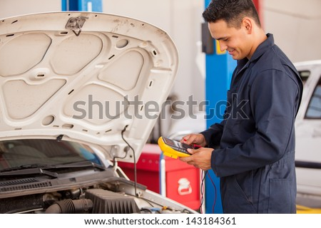 Young Latin mechanic using a multimeter to check a battery at an auto shop - stock photo
