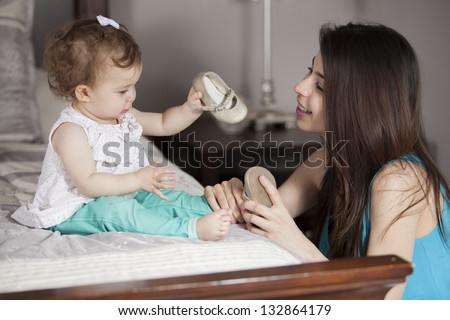 Young latin mom getting her baby girl dressed - stock photo