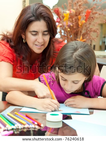 Young latin mother helping her daughter with her art project - stock photo