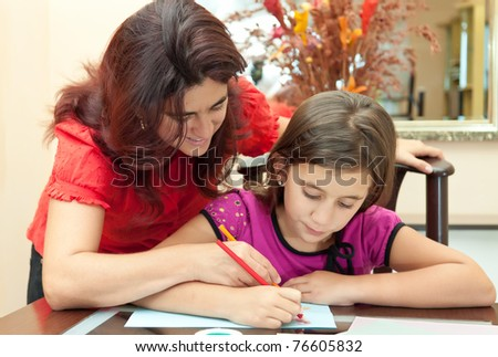 Young latin mother helping her daughter with her school homework - stock photo