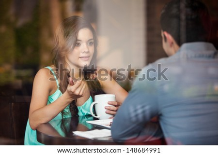 Young Latin woman eating cake with her date at a coffee shop - stock photo