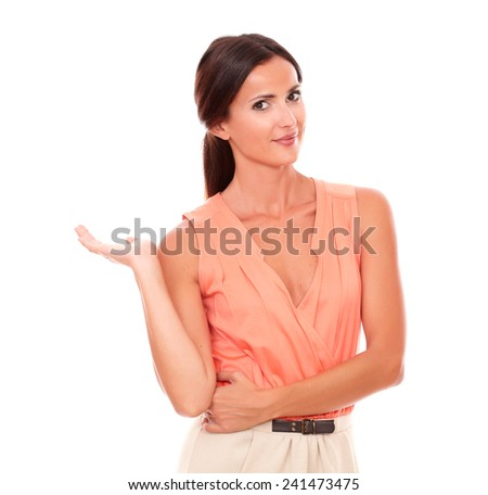 Young latin woman holding right palm up while looking at you smiling in white background - copyspace - stock photo