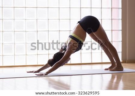 Young latin woman practicing meditation indoors. - stock photo