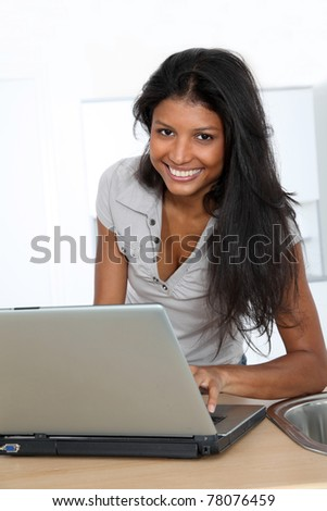 Young latin woman using laptop computer in home kitchen - stock photo