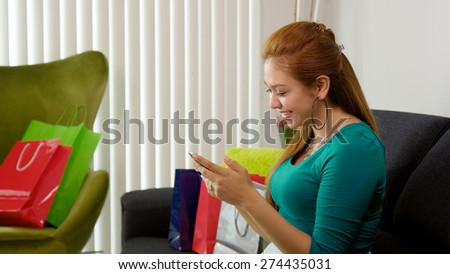 Young latina woman back at home after shopping, surrounded by bags on sofa. She holds a smartphone and types a post on social network  - stock photo