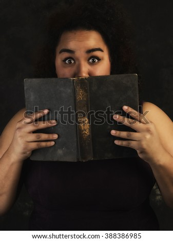 Young Latina woman in sleeveless dress holding vintage book close to her face looking fearful at camera with portrait background