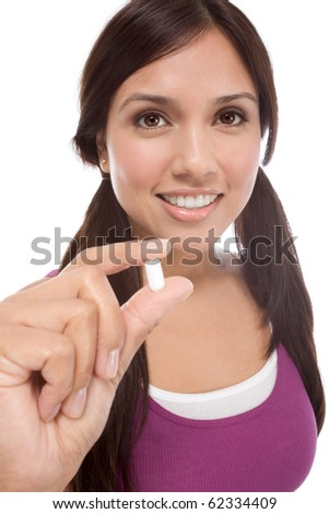 Young Latina woman showing white medication tablet - stock photo