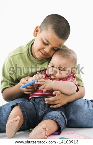 Young latino boy holding baby brother on lap. - stock photo