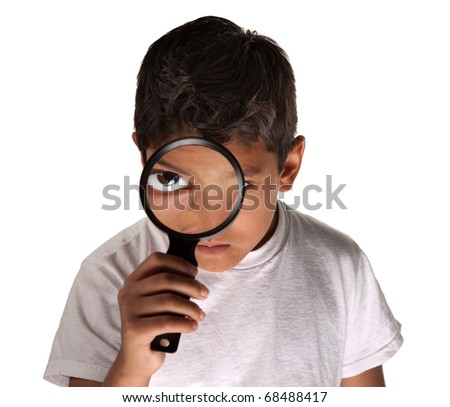 Young Latino boy looking through a magnifying glass on white background