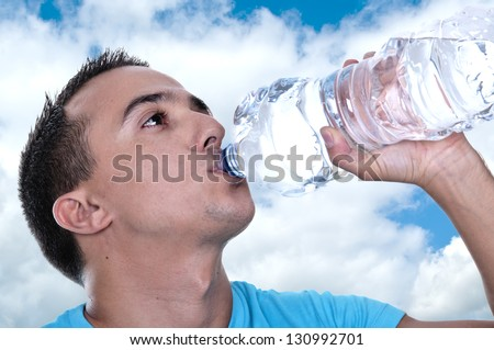 young Latino drinking water from a bottle - stock photo