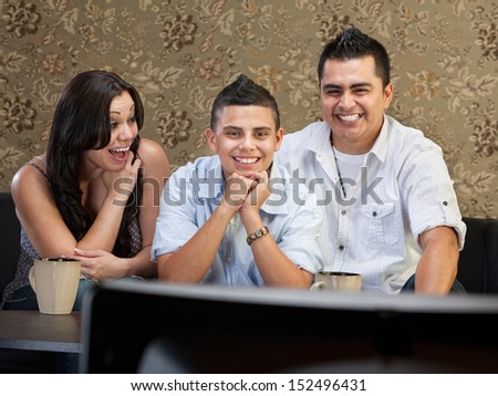 Young Latino family enjoying television indoors together - stock photo