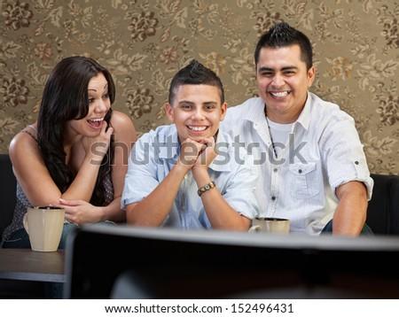 Young Latino family enjoying television indoors together - stock photo