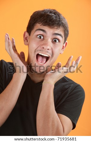 Young Latino man is very excited with hands near head - stock photo