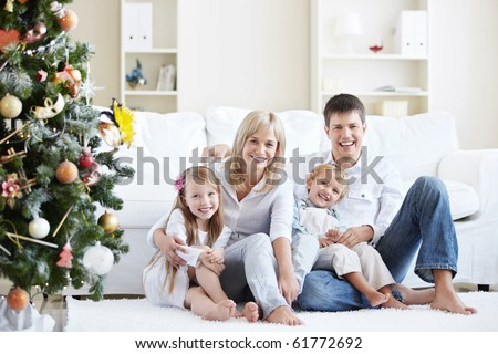 Young laughing family home with spruce - stock photo