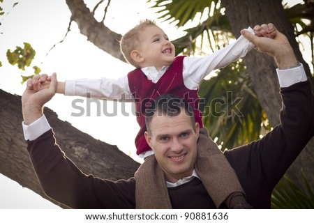 Young Laughing Father and Child Having Piggy Back Fun in the Park. - stock photo