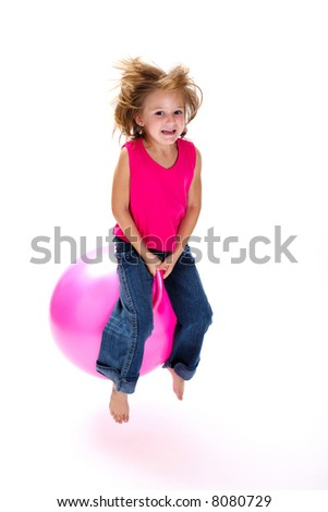 Young laughing girl bouncing on a pink space hopper