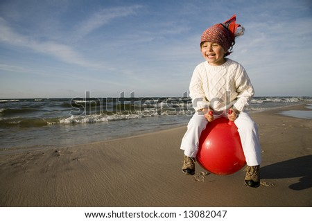 Young laughing girl bouncing on a red space hopper - stock photo