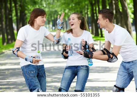 Young laughing people on rollers in park - stock photo