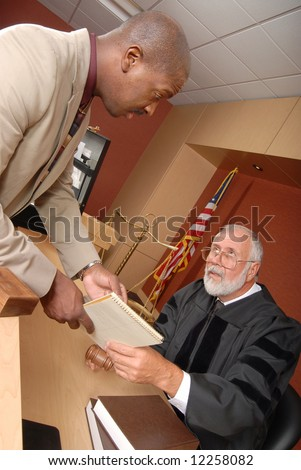 Young lawyer showing a document to the judge during trial - stock photo