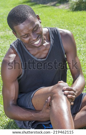 Young lean African American athlete in shorts and tank top sits on grass clutching injured knee and showing painful facial expression - stock photo