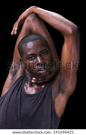 Young lean flexible sweaty athletic black man performs triceps stretch on black background