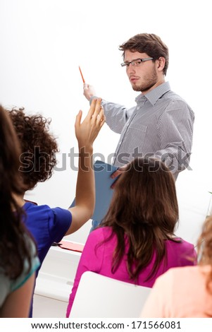 Young lecturer discussing with group of students during the classes - stock photo