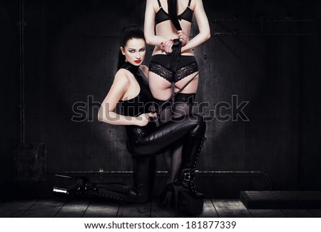 Young lesbian couple foreplay in darkness - stock photo