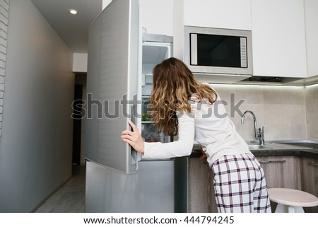 Young light brown woman in pajamas opening the refrigerator  in white kitchen at morning