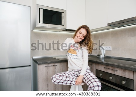 Young light brown woman in pajamas sitting on chair with white cup and catch up and yawns in white kitchen at morning - stock photo