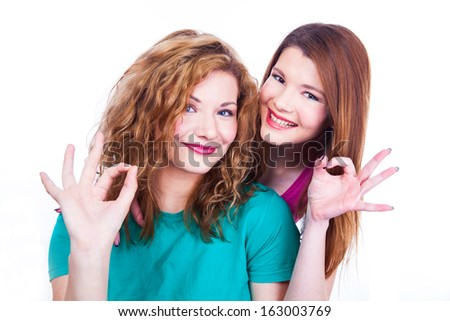 Young lighthearted girls shows Okay gesture - stock photo
