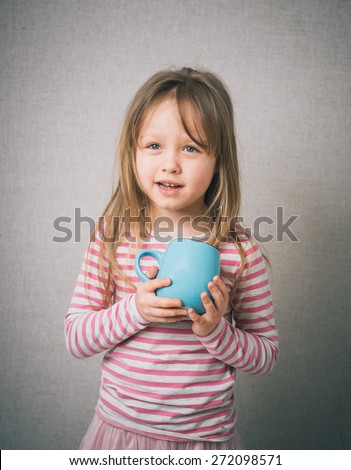 young little baby girl drinking milk glass mug coffee tea hot drink  - stock photo