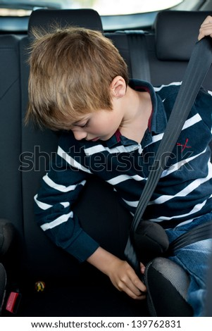 Young little boy buckled up with seatbelt inside the car - stock photo