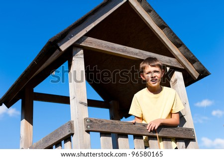 Young little boy is standing in a high seat in summer under a blue sky - stock photo