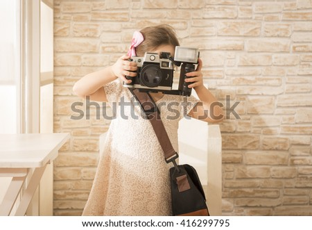 Young little girl photographer with old vintage film photo camera taking picture, indoor shot. Beautiful girl using vintage photo camera. Children's play. Art or creativity concept.  - stock photo