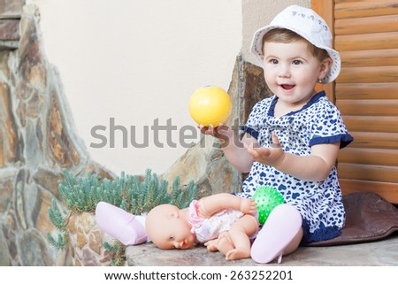 young little girl smiling and playing with ball - stock photo