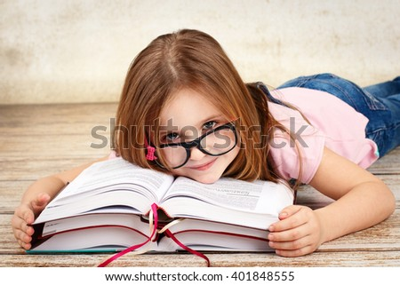 Young little girl wearing glasses and reading a book - stock photo