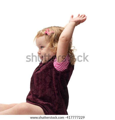 Young little girl with curly hair and hands in air in purple dress sitting over isolated white background
