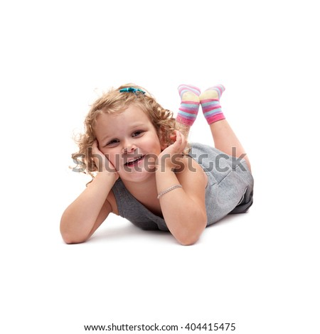 Young little girl with curly hair in gray dress lying over isolated white background - stock photo