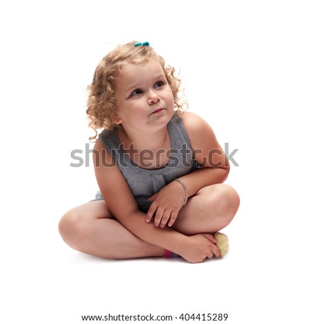 Young little girl with curly hair in gray dress sitting over isolated white background - stock photo